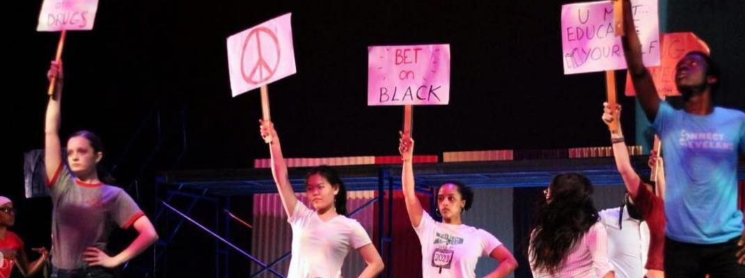 Members of Oberlin's ODC/Dance Company perform with protest signs depicting antiracist slogans